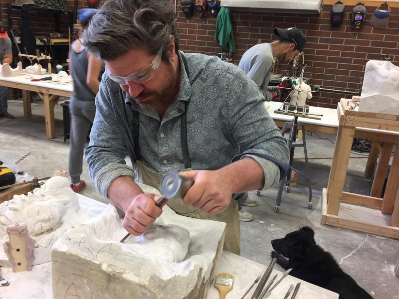 Sculptor Jason Arkles uses a hammer and chisel to carve a face in a block of Carrara marble.
