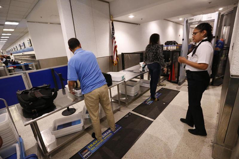 A TSA officer looks on as travelers put their items through an x-ray machine.