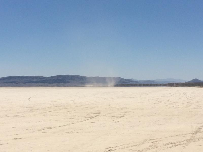 A dust devil forms on a dry lake bed in the Oregon desert.