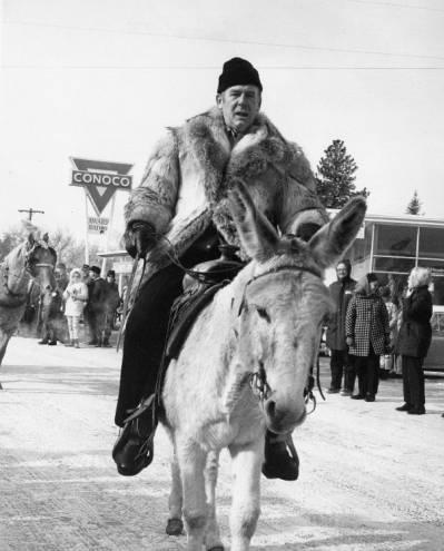 Governor Andrus rides donkey in McCall, Idaho.