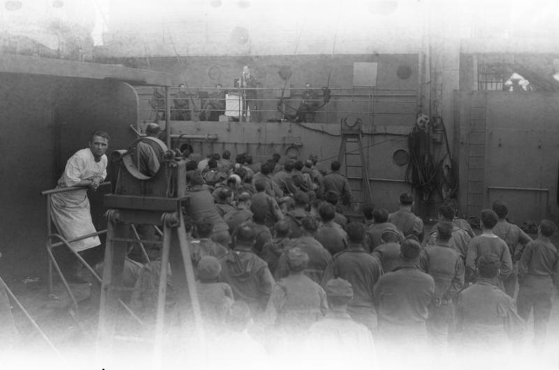 Sailors listen to an address as a cook looks on aboard a boat in WWII. Bettwieser can estimate the age of the film based on the canister it comes in, but each time he develops a batch of photos he never knows what he's going to get.