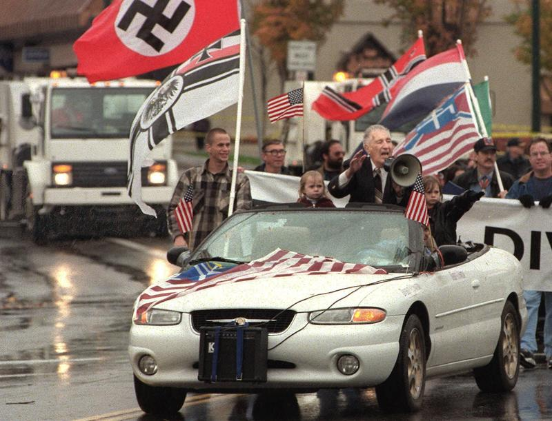 A street sweeper follows a parade led by Aryan Nation's leader Richard Butler, riding in car with a megaphone, in Oct. 2000, in Coeur d'Alene, Idaho. Butler filed for bankruptcy shortly afterwards,  days before he was to give up his 20-acre compound.