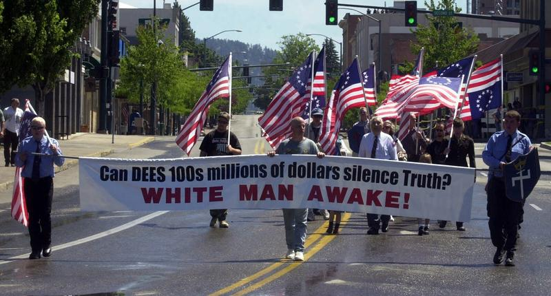 Aryan Nation members march during their annual parade in Coeur d'Alene, Idaho, Saturday, July 7, 2001. Reflecting how far the Aryan Nations has fallen since losing a $6.3 million civil rights lawsuit, only a small number of people marched in the parade.