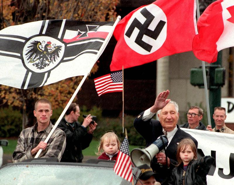 Flanked by two unidentified children, white supremacist Richard Butler waves as he leads a parade through downtown Coeur d'Alene, Idaho, Saturday morning, Oct. 28, 2000.