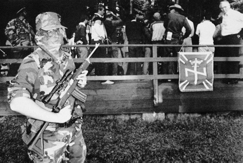 A masked guard armed with a semi-automatic rifle patrols outside the news conference as the white supremacist group, Aryan Nation, convenes its congress in Hayden Lake, Idaho, July 12, 1986.