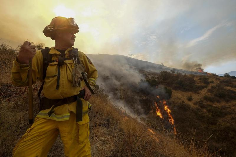 A member with California Department of Forestry and Fire Protection (Cal Fire) battles a brushfire on the hillside in Burbank, Calif., Saturday, Sept. 2, 2017.