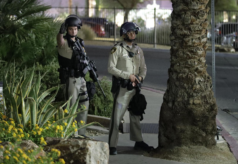 Police officers take cover behind a tree at the Luxor resort and casino during a shooting on the Las Vegas Strip, Sunday, Oct. 1, 2017, in Las Vegas