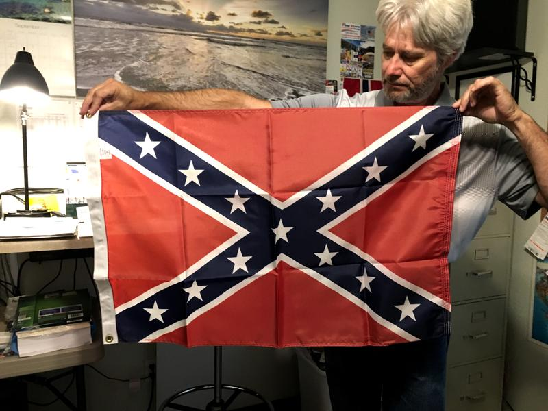 Allen Walde holds a Confederate flag in his home office in Boise. The flag store owner special orders them from a manufacturer in Georgia after some national makers dropped it from their inventory.