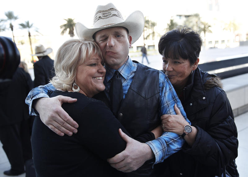 Ryan Bundy, center, is embraced by his aunts outside of a federal courthouse Wednesday in Las Vegas. Chief U.S. District Judge Gloria Navarro declared a mistrial in the case against Cliven Bundy, his sons Ryan and Ammon Bundy and Ryan Payne.