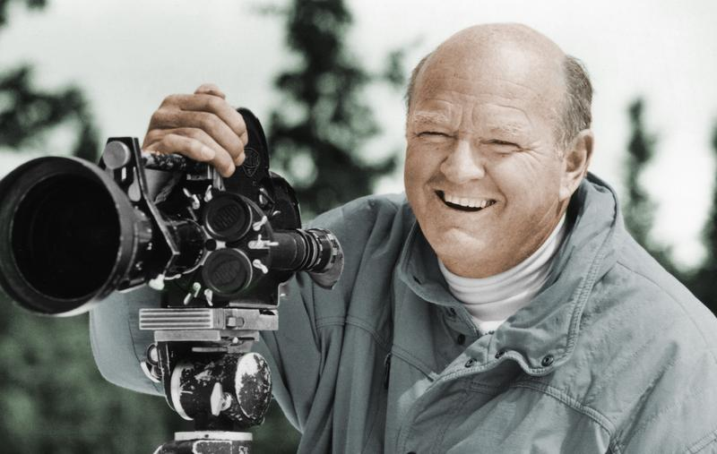 In this undated photo provided by the Warren Miller Co., Warren Miller is shown posing for a photo with a film camera.
