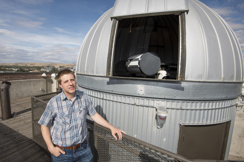 Brian Jackson stands next to the Boise State Observatory.