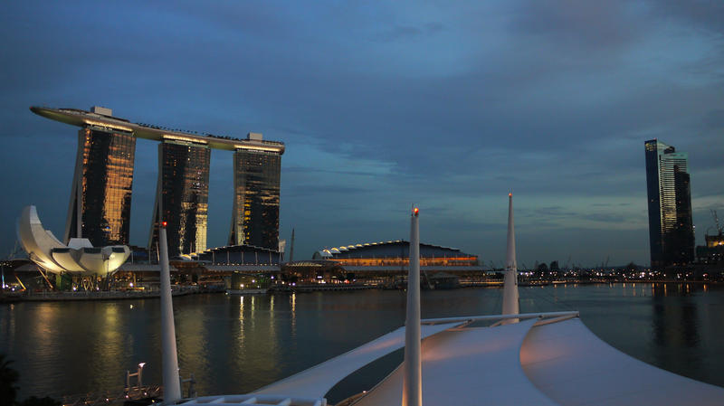 Two of Safdie's buildings in Singapore are pictured. At the bottom left of the photo is the Marina Bay Sands ArtScience Museum. Behind that, rising with three graceful towers and a suspended pool connecting them, is the Marina Bay Sands Resort.