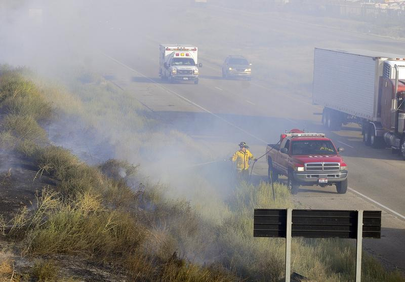 A firefighter works on extinguishing a fire on I-84 in the westbound lane near the Middleton overpass in Nampa, Idaho as an ambulance heads to an accident nearby in 2008.