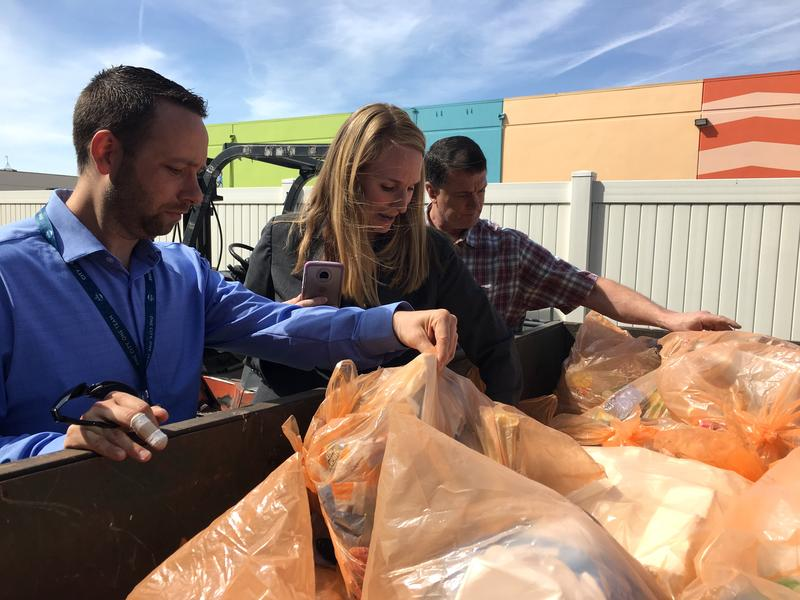 Colin Hickman (left) and Haley Falconer (middle) from the City of Boise sift through the first batch of orange bags at Western Recycling. Rick Gillihan of Western (right) joins them.