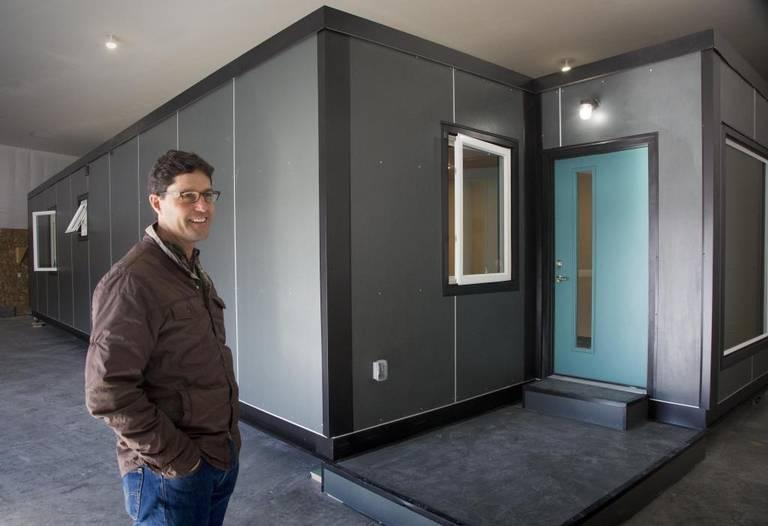 Scott Flynn, founder and CEO of IndieDwell, next to a shipping container home