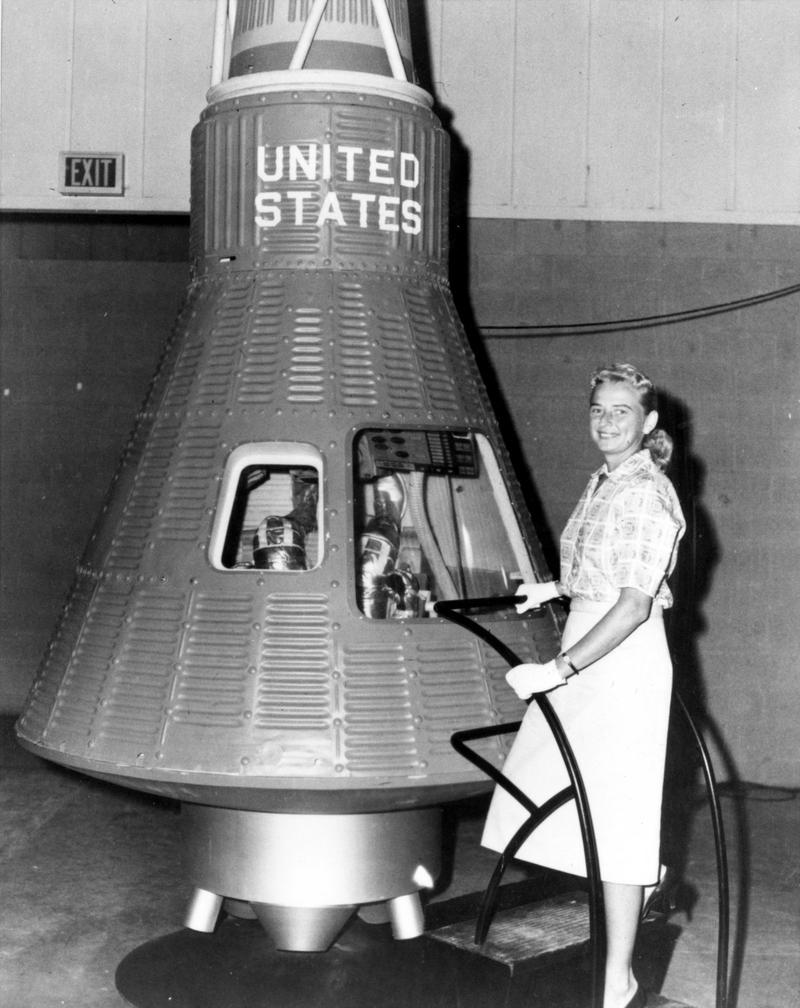 """A member of the First Lady Astronaut Trainees (FLATs), or as later dubbed """"Mercury 13,"""" aviator Jerrie Cobb poses next to a Mercury spacecraft."""