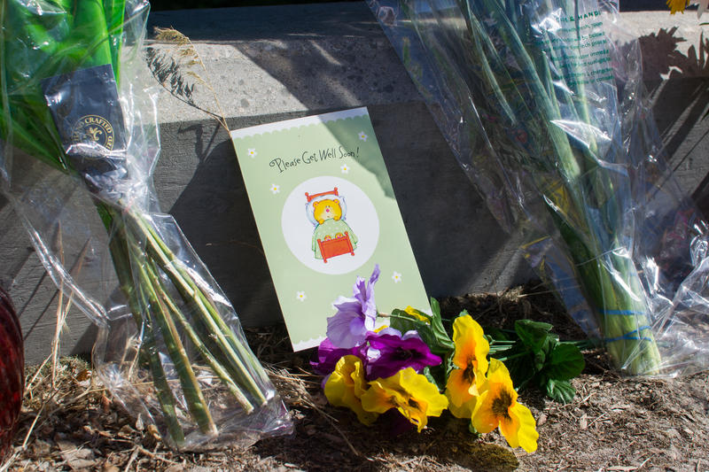 Flowers, cards and well-wishes line the street near the site where nine members of the refugee community were stabbed.