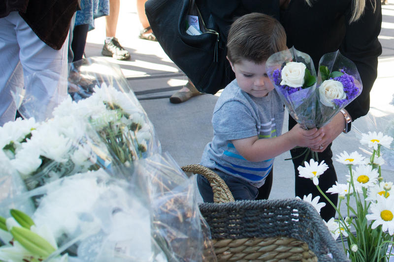2-year-old Leo Chaney and his mother, Kayla, laid flowers on the steps of Boise City Hall during a vigil for the victims of Saturday night's mass stabbing attack in Boise.