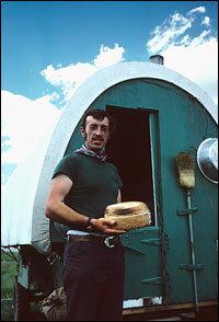 A herder holds freshly baked bread outside his wagon. The sheepwagon is a camp on wheels with beds, a table, and a wood stove. It was pulled in the early days by a team of horses and later by a pickup.