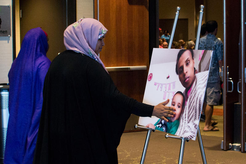 A woman taps a picture of Ruya Kadir before kissing her hand. She and hundreds of others wearing pink and purple mourned the loss of the three-year-old girl at a public memorial Saturday in Boise.