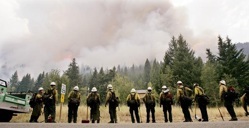 File photo of a group of firefighters watching an area of smoke and flames Aug. 30, 2007, in Ketchum, Idaho.