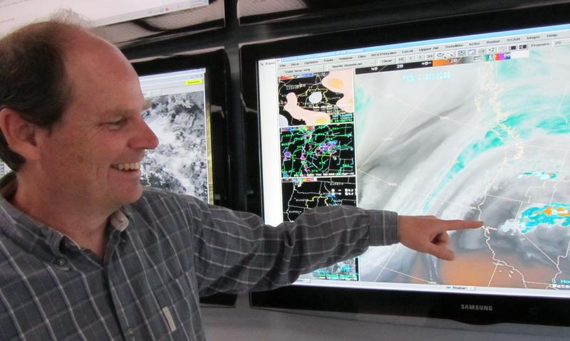 Jay Briendenbach points to a computer map of the U.S. at Boise's National Weather Service office.