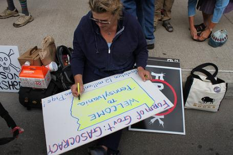 Victoria Cody works on a sign outside the hearing.