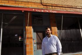 Dominic Robinson, founder of Northside UP, stands in front of the former Donzi's butcher shop in Syracuse.