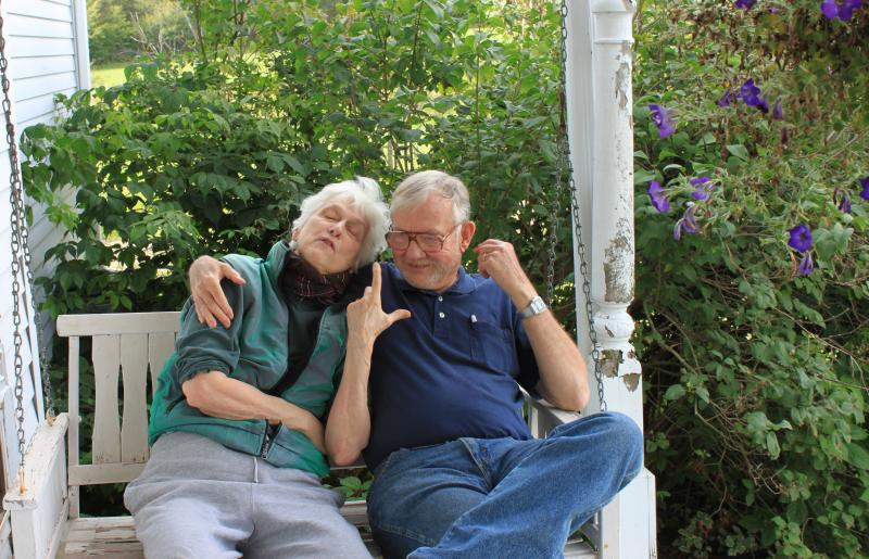 Older couple sitting on a porch swing in front of bushes.