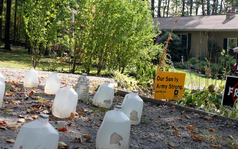 Jugs of well water on the ground outside a house