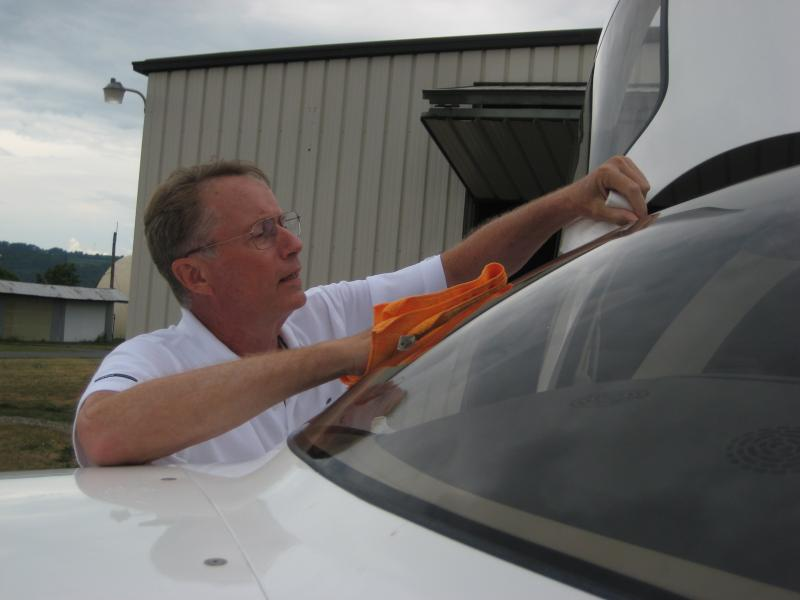 "Flight instructor Gordon ""Gordie"" Young cleans the window of the Penn Yan Flying Club's Cirrus SR-20 before flight."