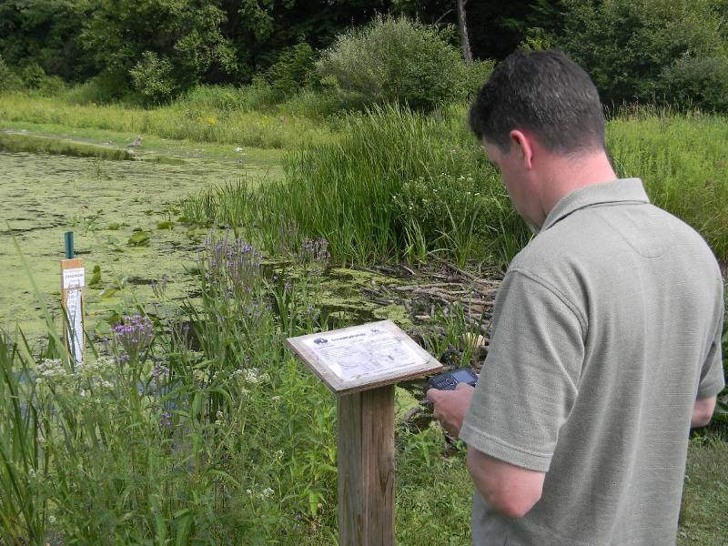 Nature center director Loren Smith texts in data about a local pond. It's part of a new research project that asks average folks with phones to report water levels around western New York.