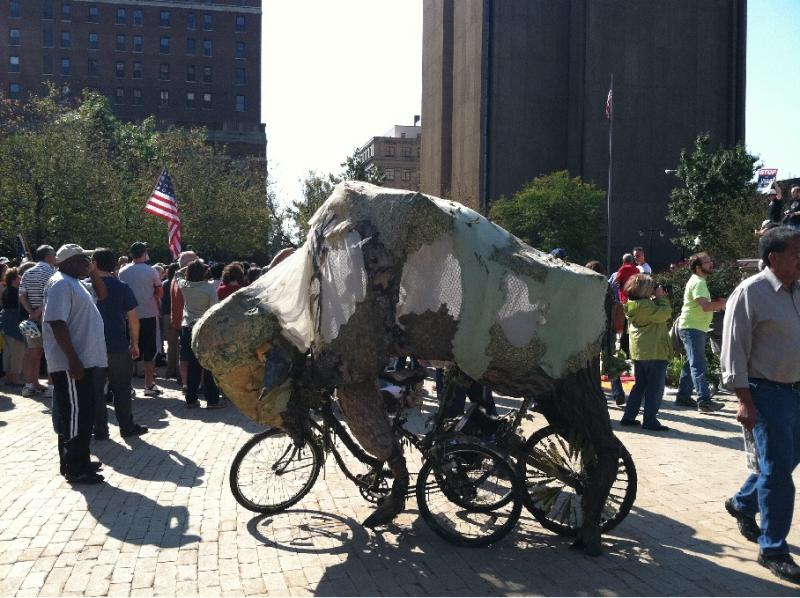 Protestor Frank Levoy rode his bicycle - modified to look like a buffalo dressed in camouflage - around the perimeter of Saturday's event, while wearing a deer skin cap.