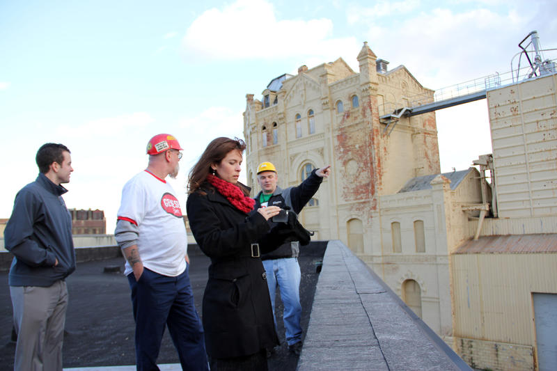 Genesee Beer Brand Manager Janine Schoos (foreground) checks a photo of the view from the future terrace of the Genesee Brew House. In the background is one of the buildings the brewery plans to demolish.