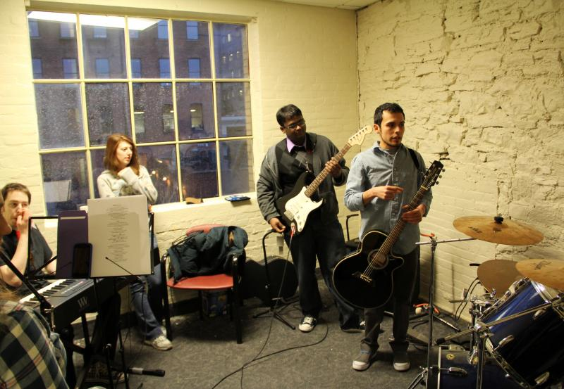 """Ivan Trevino of the Hochstein School of Music (right) leads band practice. M5 Networks employees are gearing up for a company-wide """"battle of the bands"""" in May."""