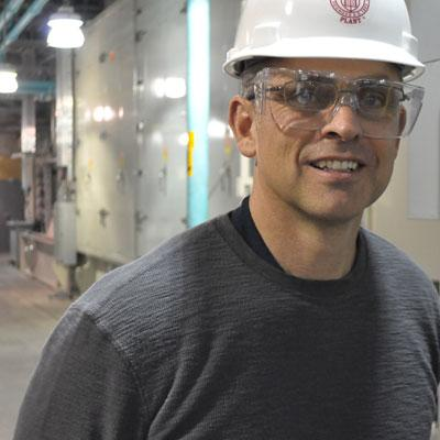 Plant manager Tim Peer stands near Cornell University's new gas-powered turbine.