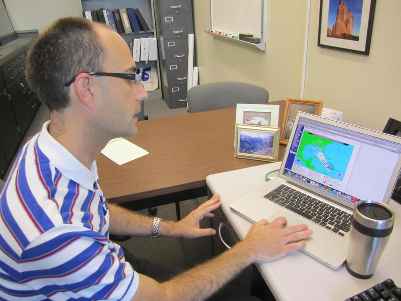 Professor Ryan Torn examines the latest predictions for Tropical Storm Isaac in his office at UAlbany.