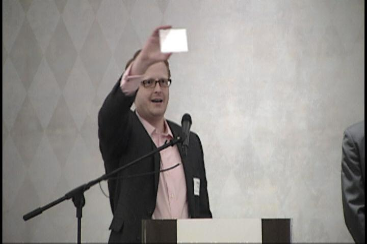 Ubiquitous Energy co-founder and CEO Miles Barr holds a sample of glass coated with photovoltaic film.