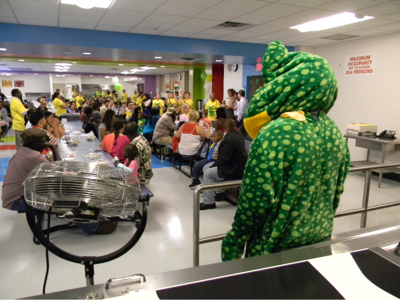 An unidentified adult dons a large plush frog outfit and high-fives students to encourage learning.