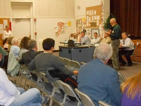 DEC spokesman Stephen Litwhiler reads out audience questions during a public meeting about pollution in the north side neighborhood at North Elementary School in Watertown.