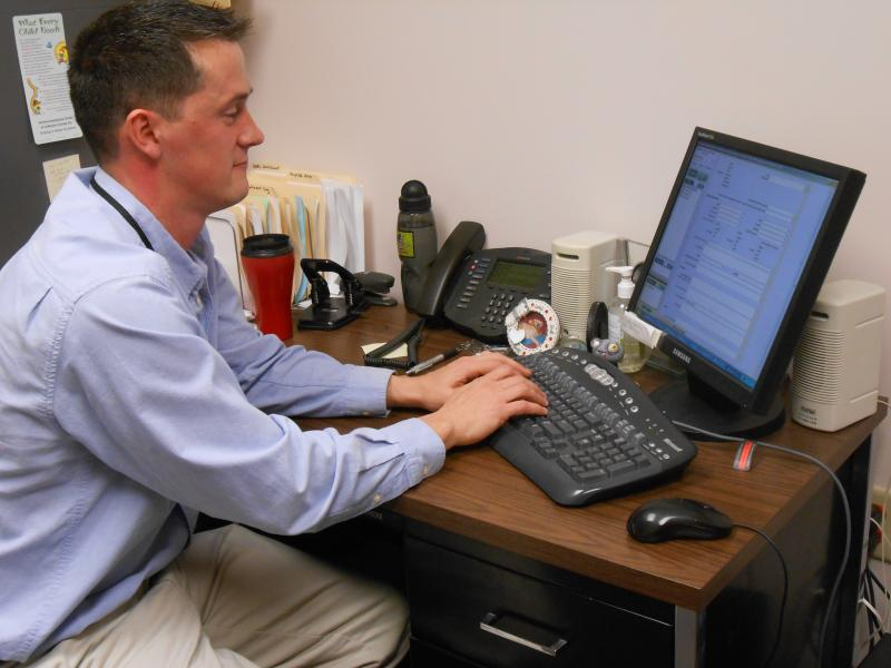 Psychologist Dan Mitchell demonstrates the North Country Children's Clinic's new electronic medical record system at his office in Watertown.
