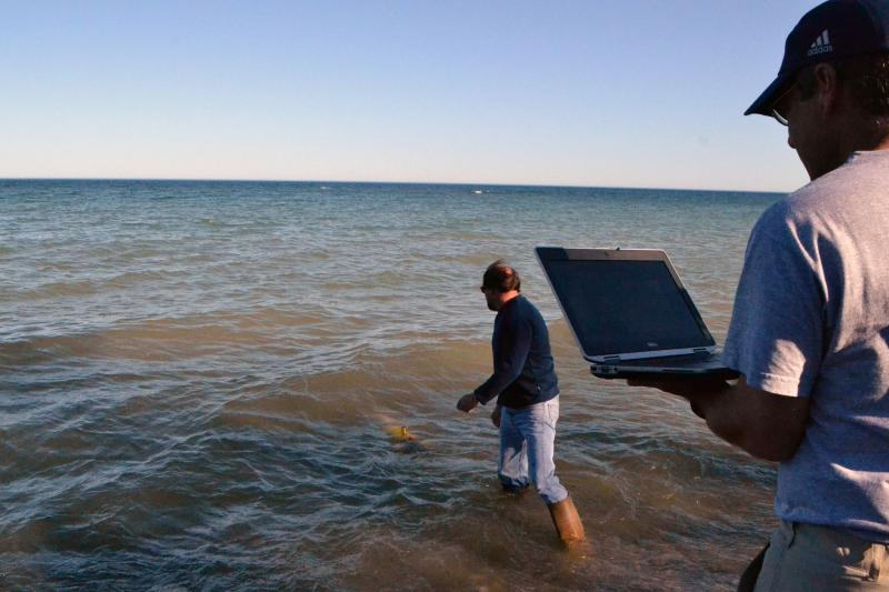 Mike Satchwell from SUNY-ESF launches a research vehicle into Lake Ontario as Russ Miller from the University of Michigan looks on.