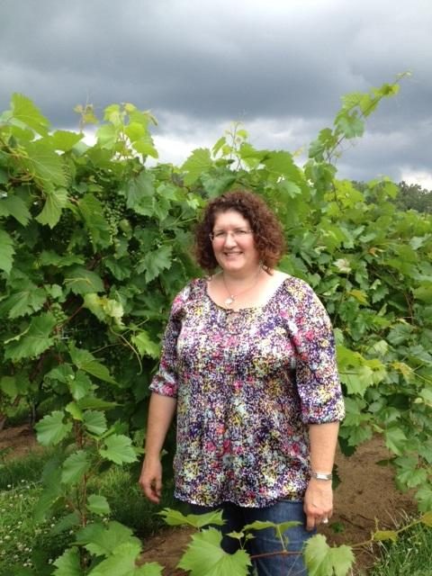 Wendy Oakes-Wilson, President of Leonard Oakes Estate Winery stands in the vineyard.