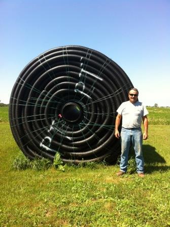 Farmer and tile drain installer Guy Palardy in front of  a roll of drainage pipe