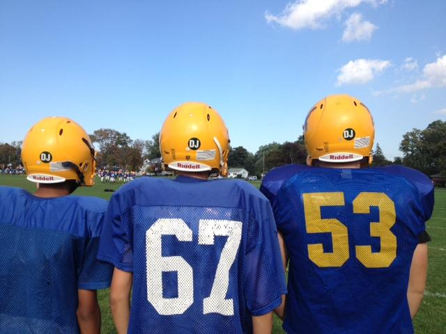 "Lockport players pose with the ""DJ"" on the back of their helmets."