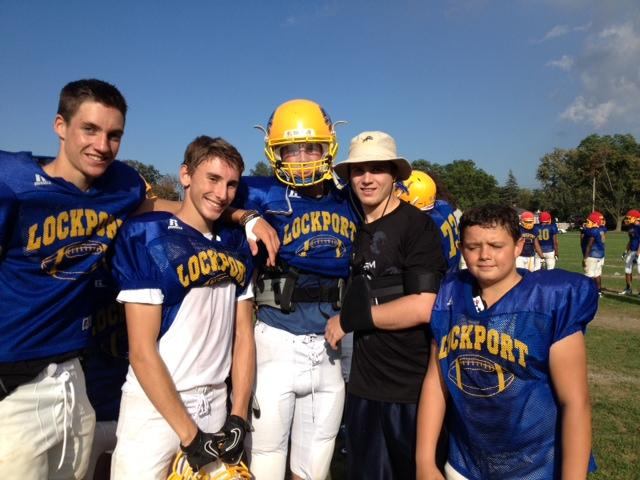Daniel Broson posing with some Lockport Junior Varsity and Varsity football players