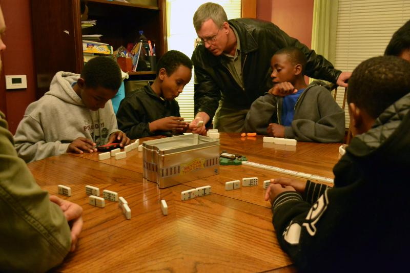 A game of dominos at HopePrint's house on the Northside of Syracuse.