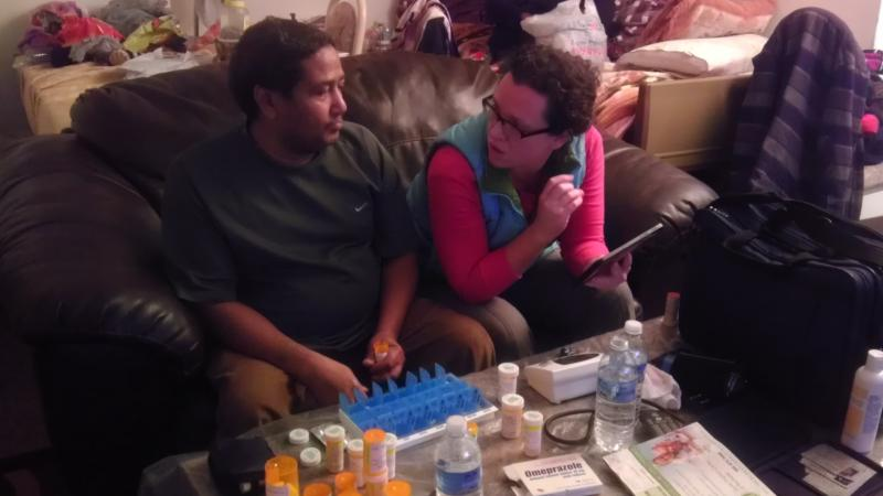 Home health nurse Sarah Miner, right, talks to Abdalla about his medicines.