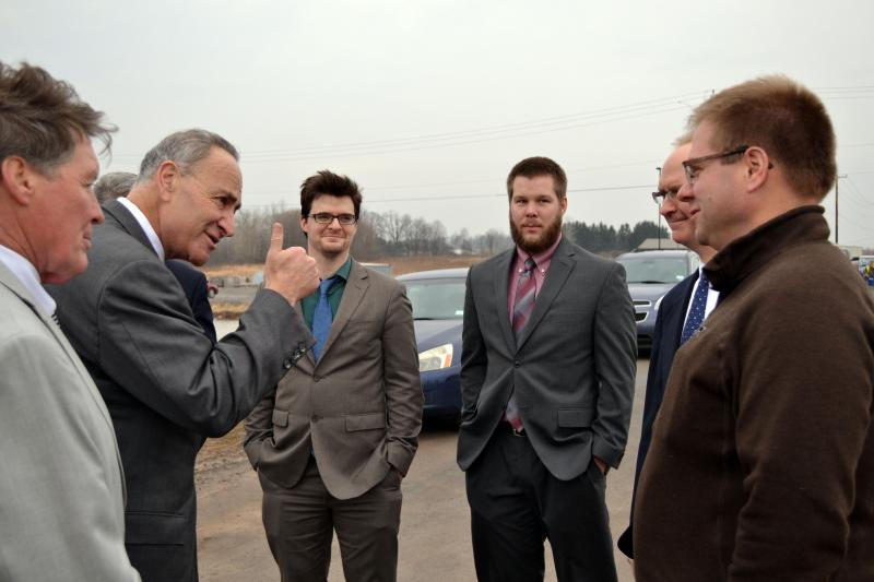 U.S. Sen. Charles Schumer (D - N.Y.), second from left, speaks with dairy farmers outside a milk processing plant being built in Auburn, N.Y.
