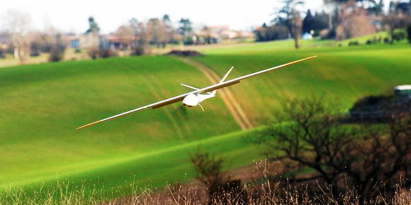 white airplane shaped drone flying over rolling green feild